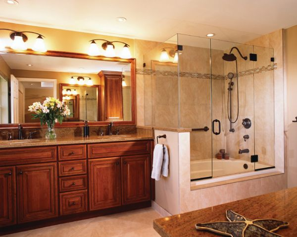 Cherry wood vanity and large glass shower and bathtub enclosure give this bathroom a classic touch
